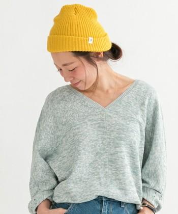 グレーのゆるニットにデニムというシンプルなスタイルに、からし色のニット帽が花を添えています。