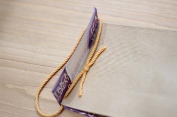 袋の中にプレゼントを詰めたら、上に飛び出た折り紙を折ってふたをします。この時、間にひもを挟んでから折ると、持ち手付きの袋になります。