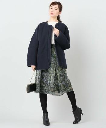 シックな色合わせには柄物のスカートを合わせて女性らしく。コートは丸みのあるシルエットで、女性の可愛らしさを演出してくれています。
