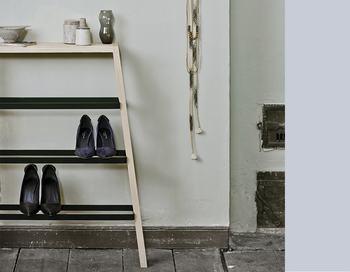 """玄関は履き物が集まるところ。靴やスリッパを整理するだけでなく、ディスプレイもできるなど、ちょっとしたお役立ち要素のあるスツールがあると便利。見せる収納と飾り棚も備わった、デンマークのデザインブランド""""ノルメード""""のシューズラックは、バーのフレームを木製の脚に留めただけのシンプル構造。壁に立てかけるだけでいいので、移動も楽々。"""