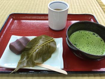 """渡月橋のたもとで、昔ながらの茶屋を営む「琴きき茶屋」。 京都屈指の""""桜もち""""の名店として知られています。和菓子店の多くは、桜の頃にしか店に並べませんが、「琴きき茶屋」では、美味しい桜もちを年中楽しむことが出来ます。  桜もちの美味しさは、桜葉の香りとほんのりとついた塩気、そして道明寺のモチモチとした食感。琴きき茶屋では、その美味しさを存分に味わえる二つの桜もちが供されます。  一つは、餡が入れずに、道明寺モチを塩漬けの桜葉に挟んだもの。もう一つは、道明寺モチをこし餡で包み、嵐山を象ったものです。桜もち好きなら、一度は口にして頂きたい名菓です。"""