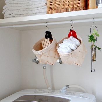 フェルトハンドル付きの小さなサイズのかごは、洗濯ばさみやリネンなどを入れて洗濯機上や脇にフックで吊るしても◎。