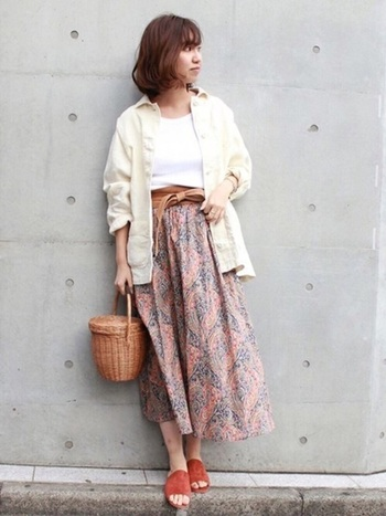 淡いペイズリー柄のロングスカートにかご素材のバケツバッグを合わせて、春らしくまとめたコーディネート。サッシュベルトとバッグのカラーがリンクしていて、統一感のある印象です。