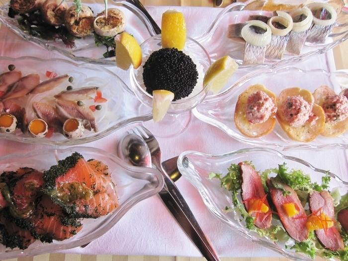 そんな店内で味わえるのは北欧のコース料理。 特にこちらの「スモーガスボード」と呼ばれるコースが人気です。 1巡目はたっぷりのキャビアにニシンの酢漬け、スモークサーモンといった冷製の前菜が。