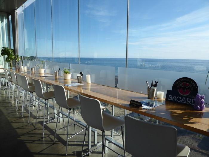 リゾート感と解放感ある店内・・・全面ガラス張り、目の前は太平洋の大海原が広がる店内は明るく開放感があり、ポップなデザイン家具やアンティークチェアーが並び楽しい雰囲気。まるでリゾートに来たかのよう。刻々と変化する風景が素敵!