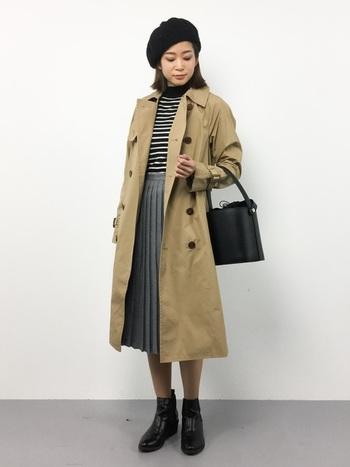 トレンチコートとプリーツスカートを合わせたフェミニンなトラッドスタイルです。バケツバッグを合わせると今年らしいトレンド感がプラスされますね。