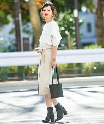 ライトトーンの爽やかなスカートスタイルに、ミニマルなバケツバッグとショートブーツを合わせています。甘辛のカラーリングのバランスが絶妙です。