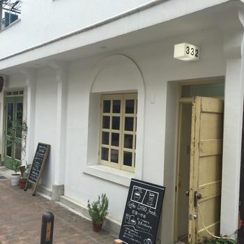 南フランスのような外観のビルの入り口。細い階段を上がると、おしゃれな隠れ家カフェが現れます。