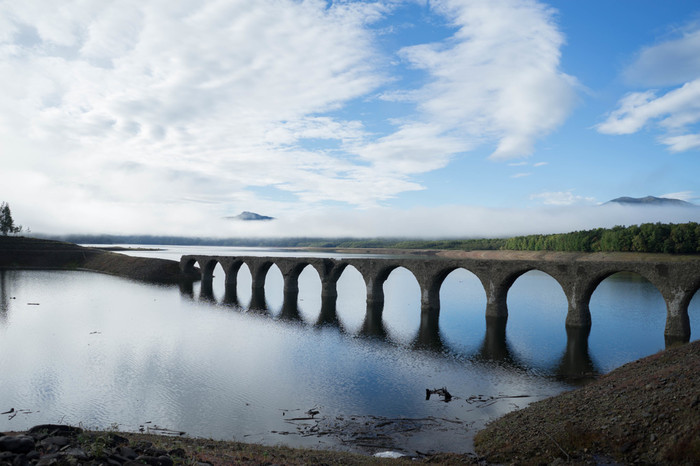 古代ローマ時代の水道橋を思わせるたたずまいで人気があります。ダムの水位が上昇する6月頃から沈み始め、8月~10月頃には湖底に姿を消す幻の橋。湖面に映り込んで真ん丸な穴が並んでいるように見えることがあり、めがね橋ともいわれます。