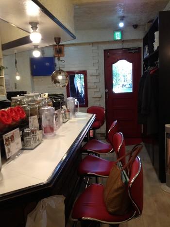 ドアを開ければ、赤と白で統一されたポップな店内がお出迎え。一気に、気分はアメリカン!?「でもココ、インド料理店やでー」