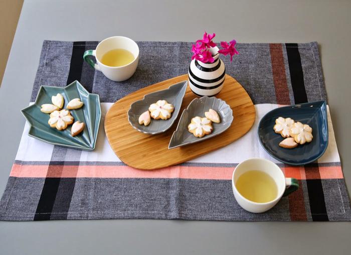 シックなお皿に桜のクッキー、冬~春の移りゆく四季を感じるランチョンマット、温もりある木のプレート、さり気ないフラワーアレンジメント…ストーリーのあるテーブルコーディネートの演出も素敵ですね。