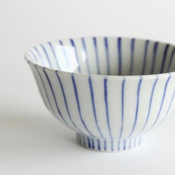 細い筆でていねいな絵付けがほどこされた九谷焼の器。白地に青のシンプルなボーダー(立縞)模様の十草柄。