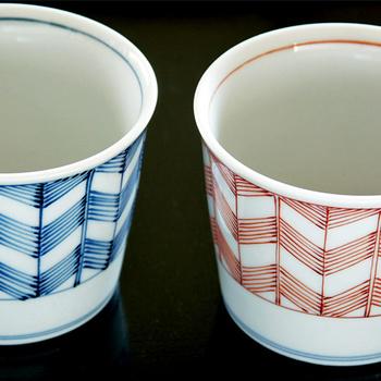 着物の柄や家紋などにも使われるシャープな幾何学模様、矢羽(やばね)紋を描いたそば猪口です。染付の青と赤絵の2個ぞろい。