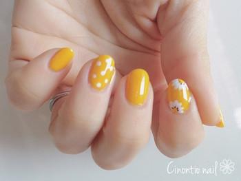 マーガレット×ドット柄のキュートなイエローの花柄ネイル。春らしいコットンワンピースに映えそうなデザインです。