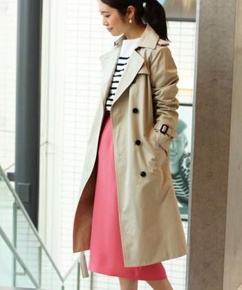 オーソドックスなトレンチコートも、鮮やかなピンクのスカートをアクセントにすると今年らしさが急上昇!