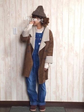 ニット帽をプラスしてカジュアルに。デニムのサロペットを合わせてかわいらしいコーデに仕上げています。ニット帽、ムートンコート、ブーツの色をブラウンでまとめて統一感を出していますね。