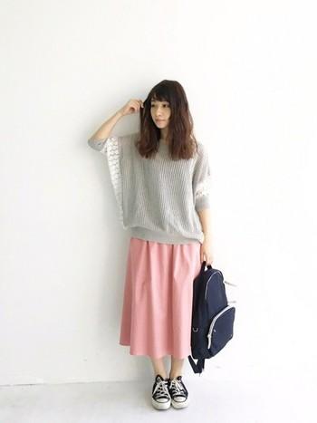 フレアーシルエットがかわいい、ピンクのミモレ丈スカートと透けニットの軽やかコーデ。小物はスニーカーとリュックを合わせて、街歩きや旅行にもおすすめです。