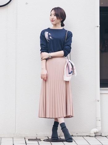 ひだが美しい淡いピンクのプリーツスカートには、女性らしいシックなネイビーの刺繍ニットを。足元はソックスにサンダルで春を先取りの大人スタイリングです。