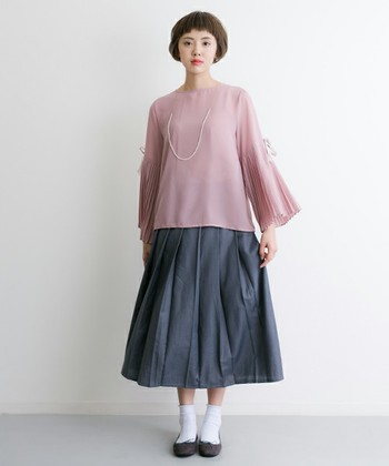淡いピンクのトップスにふんわりスカートの大人かわいいスタイリング。袖部分がプリーツになった上品なブラウスの雰囲気に合わせて、足元はパンプスとソックスで清楚に仕上げています。