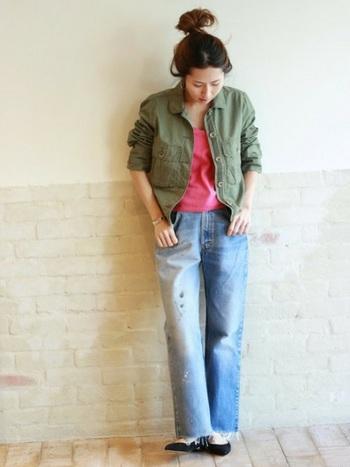 ミリタリージャケットの中に鮮やかなピンクを合わせたジーンズコーデ。ちらりと見えるピンクと足元のパンプスが、飾らない女性らしさを演出しています。