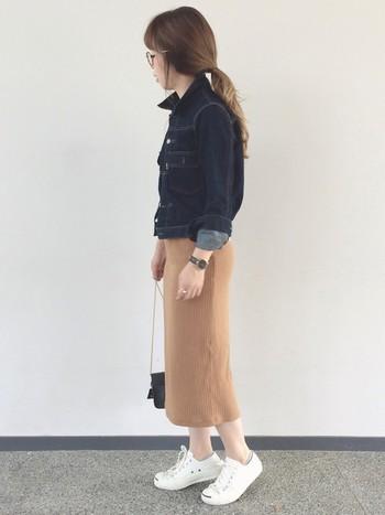 デニムジャケットにミモレ丈のリブスカート、コンパクトなショルダーポーチを合わせた大人の女性らしいスタイルです。足元は、コンバースではずして遊び心を忘れずに!