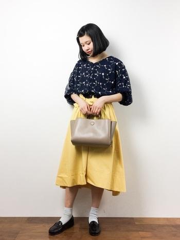 ボリューム袖の花柄刺繍ブラウスにイエローのミモレ丈スカートを合わせたスカートスタイル。足元はお約束のパンプス+ソックスでレトロな雰囲気に仕上げて。