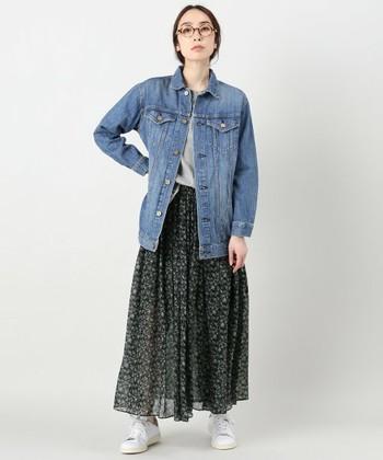 小花柄のロングスカートに、ロング丈のGジャンを合わせた抜け感のあるスタイリング。インナーはしっかりスカートにイン、そしてごつめの白スニーカーでバランスをとって◎