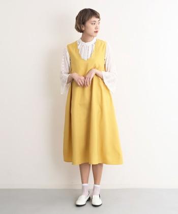 襟元のVネック部分がスカラップになったクラシカルなジャンパースカート。暖かな季節に活躍してくれる優しいイエローのジャンパースカートは一枚持っていると重宝しそうですね。