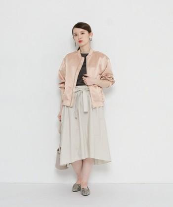 光沢のあるレディライクなピンクブルゾンにふわっとしたミモレ丈スカートを合わせて。ニュアンスカラーでまとめた甘辛ミックスはとってもスタイリッシュ。