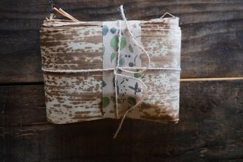 竹皮を使ったおにぎりの包み方。  水で戻した竹の皮の水けをふき取って、竹の皮の端をちょっと裂いて(5~10mm)縛るためのひもにします。 皮の内側を上にしておにぎりを中ほどにのせ、竹皮の両端をすきまのないようにしっかり折り、先にとっておいたひもでしばります。