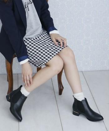 ロゴトレーナーにスカートを組み合わせたカジュアルスタイルに合わせて。ブーツから白ソックス、ジャケットからは白シャツをちらりと覗かせて、おしゃれな雰囲気に。