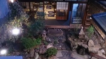 京都の町屋の縁側。石灯籠が置かれた坪庭を眺めることができます。