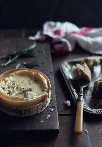 室温に戻したカマンベールチーズの表面にナイフで何本か切り込みを入れ、ローズマリーの葉を茎から外し、チーズ表面の切り込みに半分埋んで行きます。上からオリーブオイル少々をまわしかけ耐熱皿に入れ、180度に熱したオーブンで約15〜20分、チーズの中が完全に溶けて熱々になるように焼いたら完成です。仕上げに、お好みで黒こしょうをふりかけ、パンや茹で野菜などお好みの具材を絡めて召し上がれ!