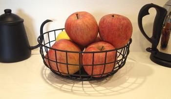すぐに食べる量の果物は小さめのカゴにいれてキッチンにおいておけば、カラフルな果物の色合いを楽しむこともできます。黒いワイヤーバスケットと鮮やかな赤いりんごがよく似合っていますね。