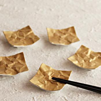 陶磁器なのに、まるで紙そのもののようなリアルな皺や質感を再現したこちらは、スーパーの紙袋から型を起こして作られたというユニークな箸置きです。和食のお膳にはもちろん、洋食のテーブルにもマッチしそうなモダンなデザイン。こちらの金のほか、銀と白のカラーバリエーションがあります。