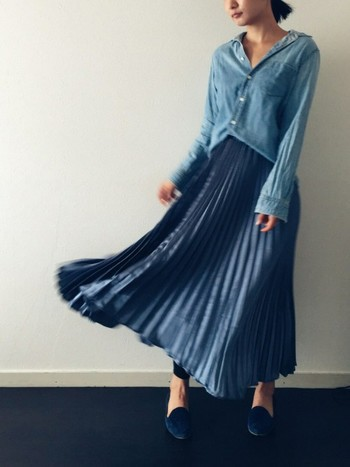 デニム素材の柔らかなシャツをブルーのロングスカートにインした、女性らしくナチュラルな雰囲気のコーデ。デニムと光沢感のある素材という、質感の異なる素材同士を組み合わせることで、着こなしにアクセントが生まれます。