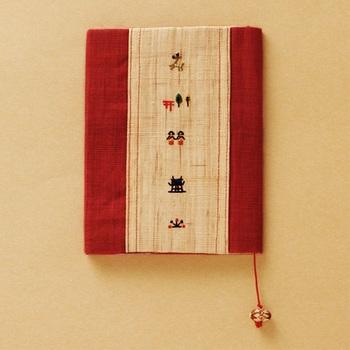 奈良絵が刺繍されたブックカバー。「手績み手織り麻」という手で紡いだ糸を手織りして作る、という全て手作業で織られた麻が使われています。江戸時代の奈良晒と同一の製法です。 コロンとしたしおりの陶玉も素敵。