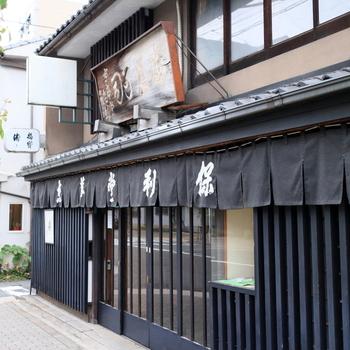 二条川畔に佇む、明治36(1903)年創業の老舗和菓子店「京華堂 利保」。武者小路千家の茶菓子を手掛ける名店です。