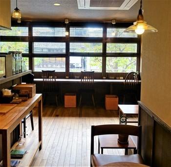 カウンター4席、テーブル4席の小さなお店「百春」。タイル貼りのビルの2階にある隠れ家的な雰囲気で、白い壁にダークブラウンのテーブルの落ち着いた空間。寺町通りが眺められる窓際のカウンター席が素敵です。