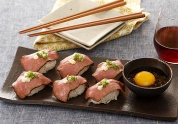 人気の肉寿司をローストビーフで。シャリはコクのあるガリバタ風味で、卵黄のタレとよく合います。