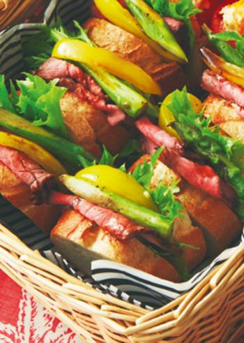 ローストビーフを野菜とともにサンドイッチに。彩り豊かで豪華なルックスは、パーティーはもちろん、持ち寄りピクニックなどにもいいですね。元気がわいてくるメニューです。