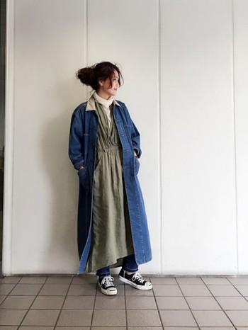 ロング丈のデニムコートにカーキ色のロングワンピースを合わせてリラックス感あふれるコーデに!裾から見えるデニムパンツがポイントになっています。
