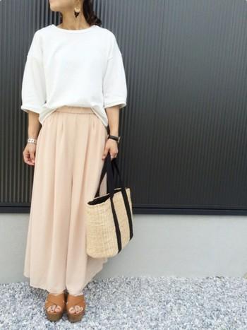 白トップスにベージュピンクのスカンツといったちょっとレディな組み合わせ♪ かごバッグとサンダルで海辺が似合います。