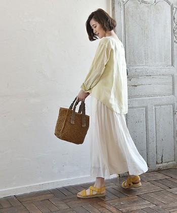 ホワイトスカートにイエローのブラウスにサンダルであわせたスタイリング。ブラウスのカジュアル感が強いため、ボトムに合わせるスカートは上品さの引き立つホワイトが◎