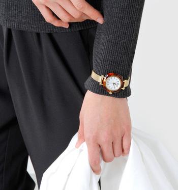 ステンレスアナログウォッチ「Helena」はゴールドとブラウンを基調とした落ち着きのあるデザインです。ベルトを留める位置を自由に変えることができるので、こんな風にお洋服の上から留めることもできます。