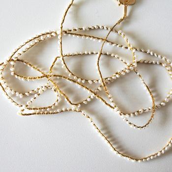 """長さ約80cmと長めの「コナユキネックレス」。こちらは、先ほどのネックレスよりも淡水パールがたくさん編み込んであります。点々と繋がれたパールがまさに""""粉雪""""のよう。"""