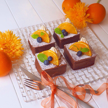 こちらのおしゃれなスクエアケーキは、牛乳パックの型に流し込んだ生地を型ごとフライパンで焼いて作ったもの。こんなにお洒落なケーキがフライパンでできるなんて、言われなければわかりませんね。生地や飾りのホイップクリームにもオレンジの果汁が混ぜ込まれていて、爽やかな香りがココアの風味との相性バッチリです。