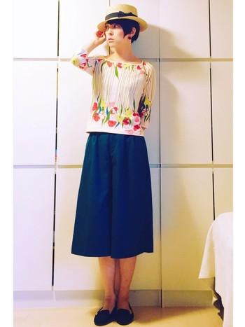 大胆に花が描かれたトップス。紺色のスカートと合わせることで、甘くなりすぎず綺麗にまとまって見えます。