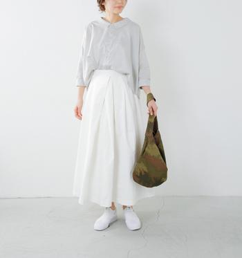 少し透け感のあるエアリーなブラウスと、真っ白なスカートを合わせて。どちらも広がりのあるアイテムなので、前をinすることでメリハリをつけていますね。アーミーな印象のバッグで甘辛に。