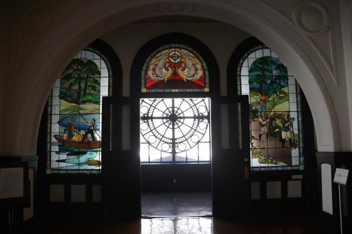 開港当時を描いた、2階のステンドグラスも必見です。左側の作品は「呉越同舟」、右側は「箱根越え」、中央上には「鳳凰」が描かれ、黄色から赤へのグラデーションが鮮やか。鳳凰の下に見える窓から外を見ると、左手に神奈川県庁(キングの塔)が見えます。